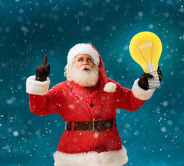 Faddish Santa Claus with open mouth and finger pointing up, showing light bulb banner. Santa Claus on blue background having a good idea. Happy New Year!