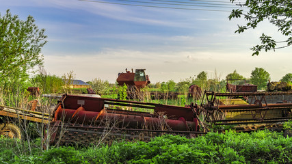 Dump the old agricultural machinery. Reaper harvester and abandoned outdated agricultural equipment.