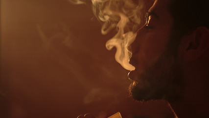 young bearded man breathes out clouds of white smoke