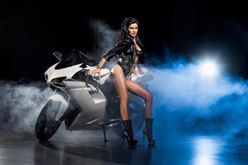 Piękna seksowna dziewczyna w skórzanej kurtce stoi przy motocyklu