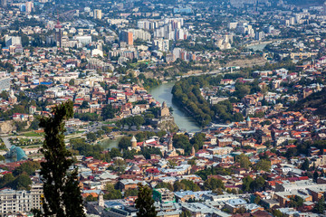 Aerial view of Tbilisi city with Kura river and Metekhi church o