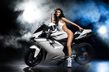 Piękna seksowna dziewczyna w białym stroju siedzi na białym motocyklu