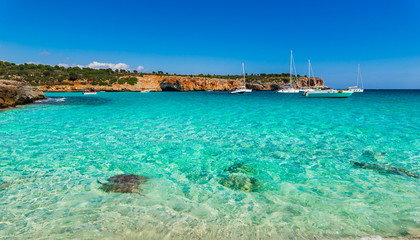 Turquoise water in the bay of Cala Varques with sailing yachts at Majorca Spain