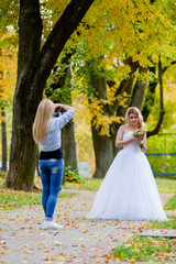 Wedding photographer is shooting portrait of the bride in the autumn park