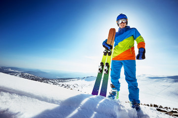 Happy skier in colorful clothes with ski