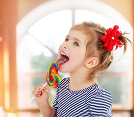 Girl licks candy on a stick