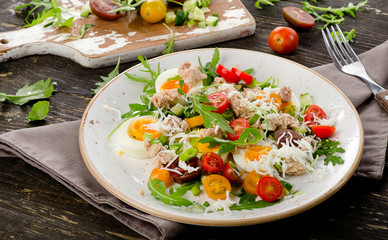 Fresh salad with fish, eggs and tomatoeson  rustic wooden backgr
