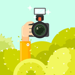 Photographer hand holds photo camera vector illustration. Spy hides in green bushes with photo camera. Journalists sit in ambush and make sensational shot. Photographer concept in flat style