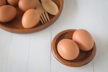 Egg in a wooden bowl on wooden table white. Chicken Egg. Top view with copy space