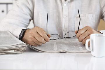 Man reading newspaper and holding eyeglasses