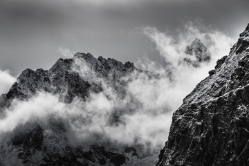 black and white photo of snow covered rocky mountain peaks with fog