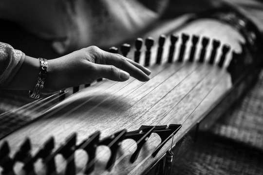 Woman play a traditional korean string instrument : the gayageum