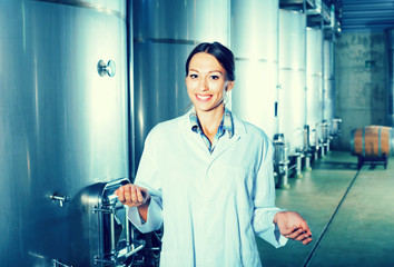 Portrait of woman standing on wine factory in secondary fermenta