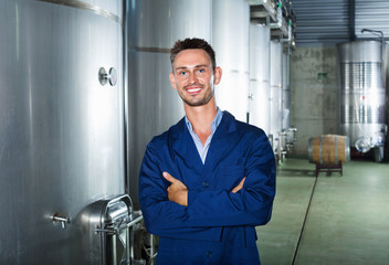 Portrait of man winery worker on wine factory in secondary fermentation section