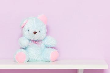 Blue teddy bear on shelf.