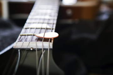 Acoustic guitar with piectrum close up in dark background