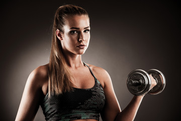 fit woman workout with dumbbells in gym studio photography of a