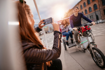 Female taking photographs of friends on tricycle
