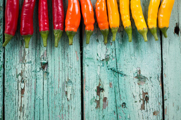 many vibrant colors on peppers , old wooden background
