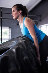 Female athlete pushing tire in gym