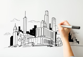 close up of hand drawing city on white board