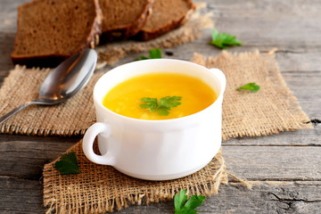 Pumpkin soup with potatoes and rice. Pumpkin soup in a bowl, spoon, bread slices on old wooden background. Vegetarian recipe. Closeup