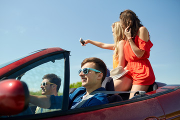 friends driving in cabriolet car and taking selfie