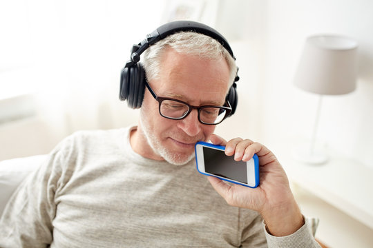 happy senior man with smartphone and headphones