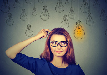 woman in glasses looking up light idea bulb above head