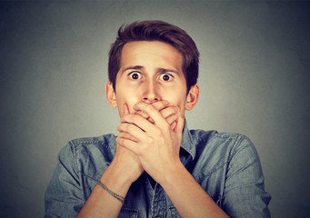 shocked young man covering his mouth with hands