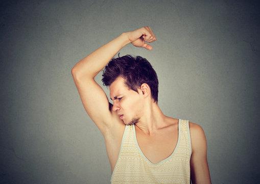 man, smelling, sniffing his armpit, something stinks bad, foul odor