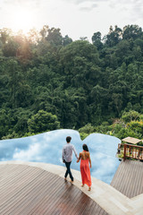 Young couple walking towards pool at luxury resort