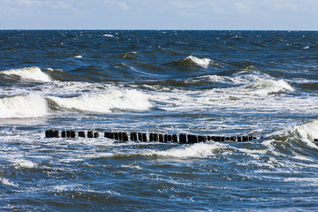 Stormy sea, waves and breakwater