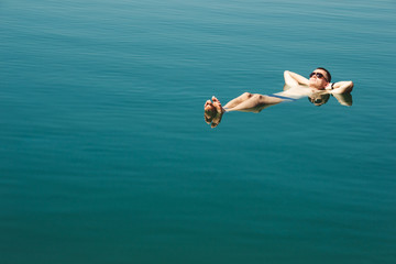 Man floating and relax in water Dead Sea. Tourism recreation, healthy lifestyle concept. Copy space. Focus on feet