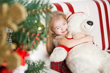Homemade Christmas, girl hugging a teddy bear.