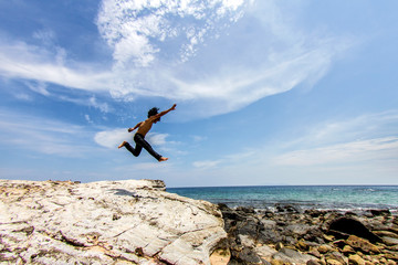 Man jumps from a cliff into the sea and blue sky background