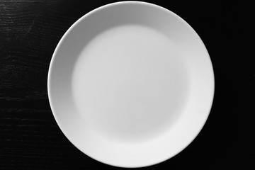 Empty white plate on black wooden table Wall mural