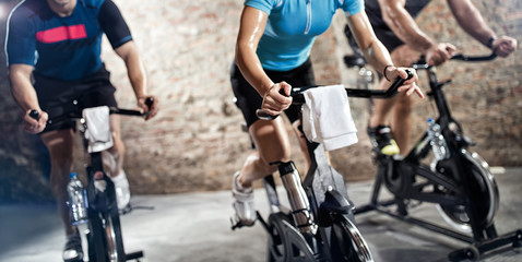 sports clothing people riding exercise bikes