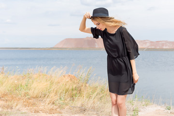 beautiful young blond woman in a black dress and a light black hat in the desert and the wind blowing her hair in a hot summer day