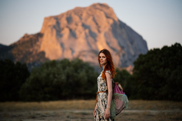 A young woman traveling in the summer in the mountains