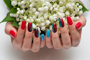 exclusive red blue manicure with foil on the long square nails holding flowers
