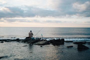 Shore sea and fisherman