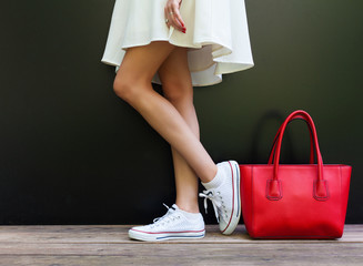 beautiful fashionable big red handbag standing next to leggy woman in white short dress and white sneakers
