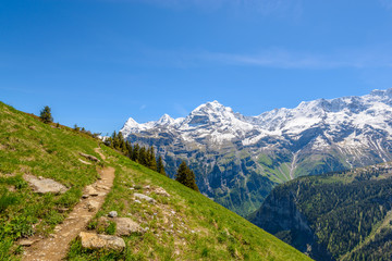Beautiful landscape of valley in Alpine mountains, small trail, hike root, majestic picturesque view in sunny day Wall mural