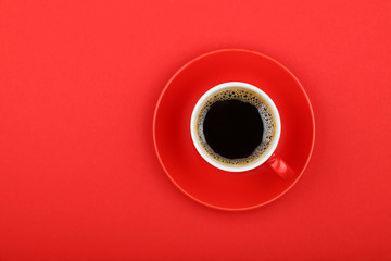Americano coffee in full cup with saucer on red