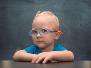 Smart kid wearing glasses with red pencil behind his ear sits at a table on a background of chalkboard