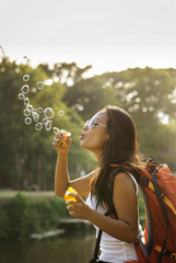 Playful woman blowing bubbles against sky on sunny day