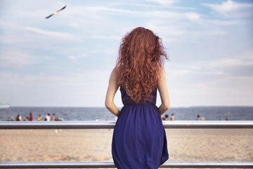 Rear view of young woman standing by railing against sky