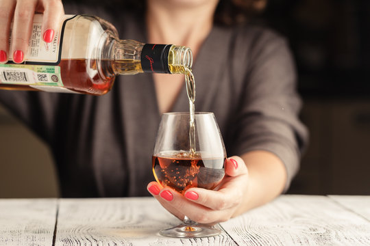 Alcoholism issue. Female take wine glass on dark toned table