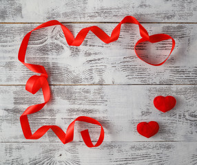wooden background with red ribbon and candy hearts